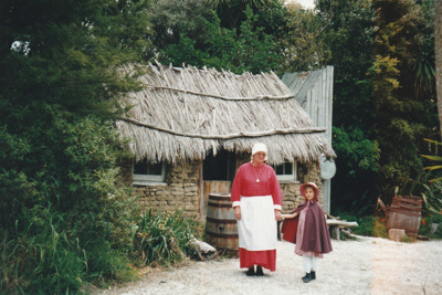 A lady and girl in costume outside the Sod Cottage, Howick Historical Village on a Live Day.; La Roche, Alan; P2020.43.34