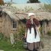 Vicki Blythe-Pope in costume, holding a broom and a bucket in front of the sod cottage in the Howick Historical Village. ; La Roche, Alan; 2010; P2020.50.24