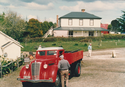 A vintage truck (OC4815) at Howick Historical Village on a Live Day. Bell House is i the background.; Ashby, Muriel; P2021.108.20