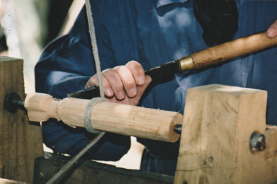 Close up of Grant Christianson, working as a bodger on a pole lathe at Howick Historical Village.; La Roche, Alan; P2021.87.04
