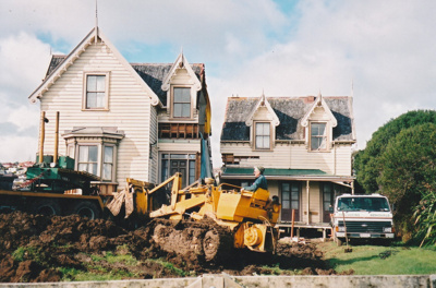 A bulldozer working on the ground in front of the halves of Puhinui on its new site in the Howick Historical Village.; Alan La Roche; May 2002; P2020.11.30