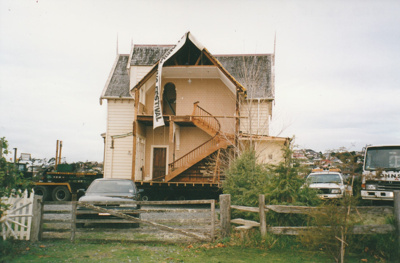 Side view of half of Puhinui being on its new site in the Howick Historical Village. Trucks and two cars parked nearby.; Smith, Malcolm; May 2002; P2020.16.15