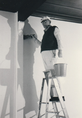 Toby Gilmour wallpapering the drawing room in Puhinui.; July 1991; P2020.14.33