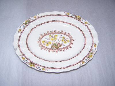 Small white dish with yellow flowers and maroon/br...