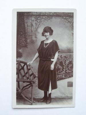 Postcard of a woman posing against a garden backdr...