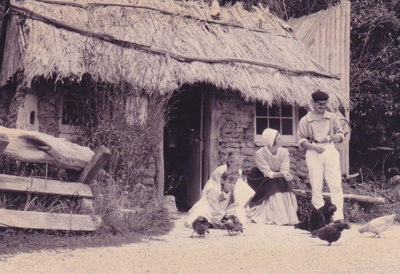 A lady, man and 2 girls in costume outside the Sod Cottage, Howick Historical Village on a Live Day.; La Roche, Alan; P2020.45.02