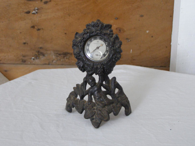 Small clock in decorative steel stand.
