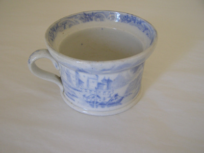 A white sugar bowl decorated with blue oriental im...