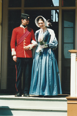 Linda Frazerhurst as a young lady with her escort Matthew Bonnet as her escort from the 65th regiment on the Puhinui verandah on an HHV Live Day. ; Palmer, Ros; October 2003; 2019.198.14