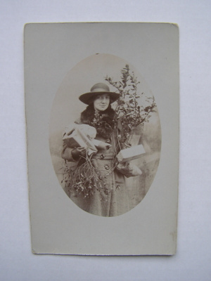 A post card depicting a woman wearing a coat and h...