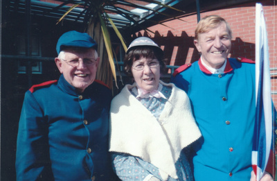 Alan la Roche, Coralie Nelson and Wally Rice (the men in Fencible uniform) holding the Union Jack outside the Howick Library in Uxbridge Road. Close-up of previous photo.; October 2013; P2021.119.02