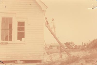 David Mirams, Peter Wren and John Mirams up ladders working on  Pakuranga School at the Howick Historical Village. ; 17 March 1979; P2020.51.10