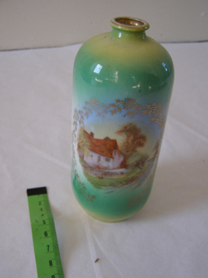 small green vase with painted cottage scene.
