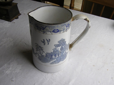 metal jug painted white with blue design