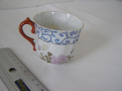 ceramic teacup with flowers and blue pattern aroun...