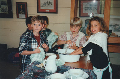 """Children doing the dishes after a 'sleepover"""" holiday programme in Pakuranga School in the Howick Historical Village.; P2020.66.01"""
