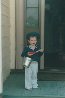 Elijah holding a bucket and spade on the Puhinui verandah on an HHV Live Day. ; Palmer, Ros; October 2003; 2019.198.18