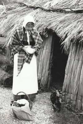 A woman in costume outside the Sod Cottage, Howick Historical Village. ; May 1995; P2020.45.09