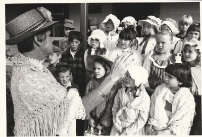 A school group,all in costume, singing outside Brindle Cottage in the Howick Historical Village. ; N.Z. Herald; P2021.39.01