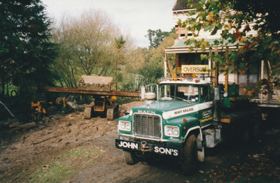 A Johnson's Heavy truck and trailer moving half of Puhinui to its new site in the Howick Historical Village. A bulldozer is working alongside.; Smith, Malcolm; May 2002; P2020.16.09