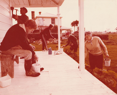 Volunteers painting the Vicarage at the Historical Village. Bell House is behind.; NZ Women's Weekly; 1978?; P2020.26.04