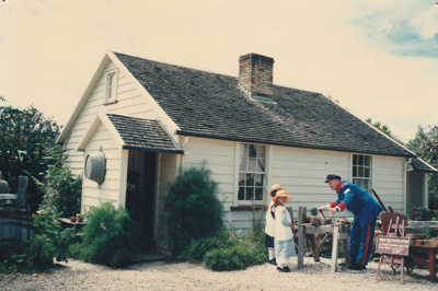 Ray Burgess at the grinding wheel outside Briody-McDaniel Cottage.  ; La Roche, Alan; c1990