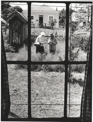 Two volunteers in costume in the garden behind Maher-Gallagher Cottage in the Howick Historical Village.; Eastern Courier; P2020.94.01