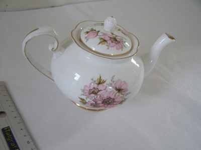 White ceramic teapot with pink roses.