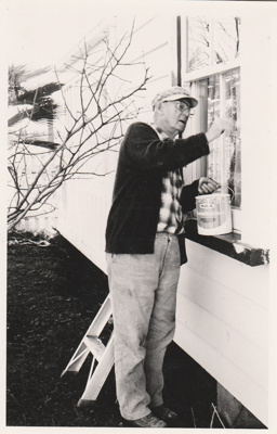 Toby Gilmore painting the windows of brindle Cottage in the Howick Historical Village.; 1987; P2021.26.01