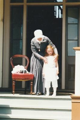 Jeanette Claridge dressing Amelie  on the verandah of Puhinui on an HHV Live Day. ; Palmer, Ros; October 2003; 2019.198.06