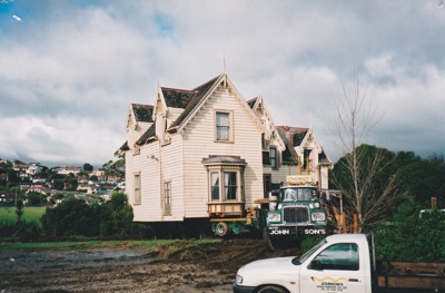 A Johnson's truck and a pilot vehicle in front of Puhinui on its new site in the Howick Historical Village.; Alan La Roche; May 2002; P2020.11.43