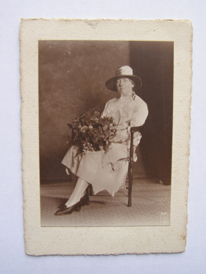 Photograph of sitting woman holding a bouquet of flowers; 2012.36.1