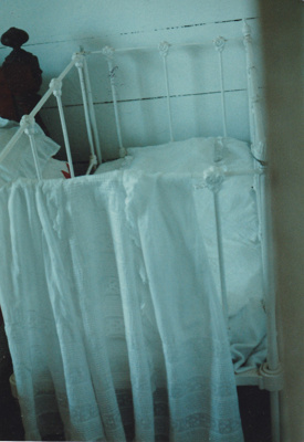 A Baby's cot in the bedroom in Briody-McDaniel Cottage.  ; La Roche, Alan; November 1989; P2020.104.10