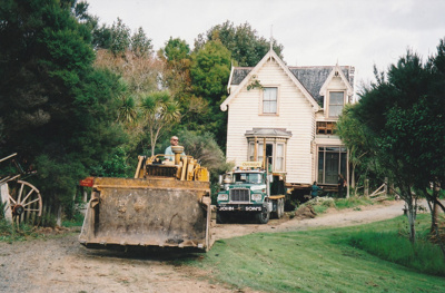 A bulldoze, showing the driver,r preparing the way for a Johnson's Heavy truck and trailer to move Puhinui to its new site in the Howick Historical Village.; Alan La Roche; May 2002; P2020.11.28