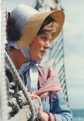 The November 1977 150th re-enactment of the Fencible and early settler landing at Cockle Bay. Shows Jane Martensen, in costume, on the ship.; Eastern Courier; November 1977; P2021.93.11
