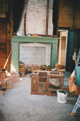 The fireplace in Puhinui kitchen being bricked by Gary McCarthy. The old coal range is on the floor and workmen's tools are strewn about.; Alan La Roche; September 2003; P2020.14.18