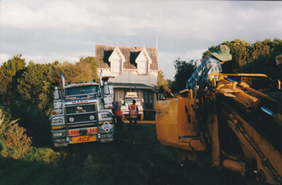 A Mack Truck towing heavy vehicle following a bulldozer clearing the way for moving half of Puhinui to its new site in the Howick Historical Village. A Johnson's truck carrying the building is in the rear.; Smith, Malcolm; May 2002; P2020.16.06