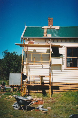 The chimney of the Puhinui kitchen fireplace under construction by Gary McCarthy.Showing the outside view with scaffolding, wheelbarrow and bricks.; Alan La Roche; September 2003; P202014.17