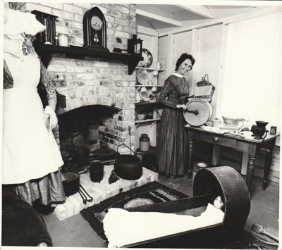 Pam Taylor in costume, churning butter inside Briody-McDaniels Cottage, formerly McDermott's Cottage at Howick Historical Village.  ; NZ Women's Weekly; January 1980; P2020.101.01