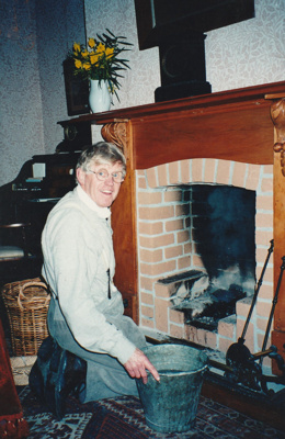 Alan la Roche cleaning out the fireplace in Puhinui.; O'Halloran, Esme; August 1995; P2021.109.01