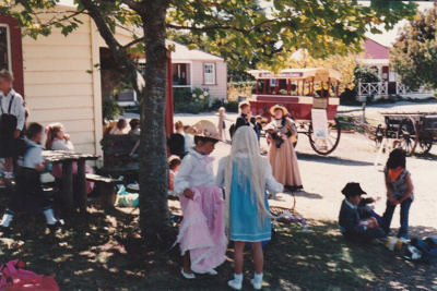 A group of school children, in costume, outside Brindle Cottage in Howick Historical Village.; 1995; P2021.107.20