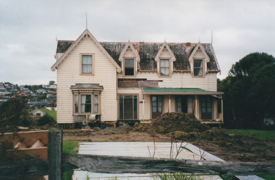 Puhinui, rejoined, on its new site in the Howick Historical Village. A concrete mixer is in front of the homestead. Also shows a pile of earth and building materials.; Smith, Malcolm; May 2002; P2020.16.20