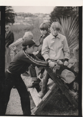 A boy trying his hand at sawing wood on a craft day at Howick Historical Village, August 1983.; Spencer, LInda, East City News; August 1983; P2021.172.01