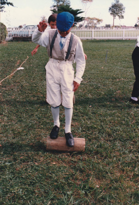 A boy in costume playing roll the log on a Live Day  in Howick Historical Village.; c1999; P2021.121.05