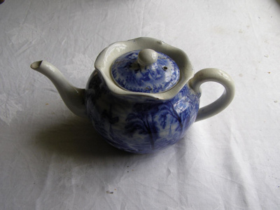 Ceramic teapot with blue willow design.