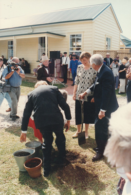 Marin Burgess and Sir Barry Curtis planting at tree at the opening of White's Homestead at Howick Historical Village.; La Roche, Alan; 16 March 1997; P2021.74.02