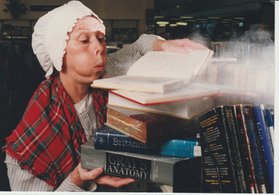 Marie Sturgess blowing dust off books at Howick Historical Village.; Eastern Courier; 2019.131.01