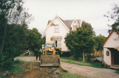 A bulldozer making a pathway for half of Puhinui being moved to its new site in the Howick Historical Village. passing the Dame school.; Smith, Malcolm; May 2002; P2020.16.12