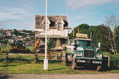 Johnson's truck moving half of Puhinui onto its new site in the Howick Historical Village. ; Alan La Roche; May 2002; P2020.11.12