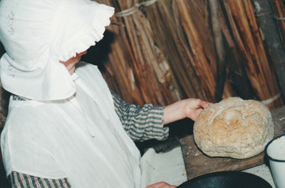 A girl in costume, with bread on a Live Day in Howick Historical Village.; La Roche, Alan; P2021.98.08